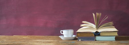 open book and cup of coffee cup on red grungy background, good copy space