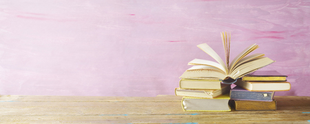 open book on a stack of books,purple grungy background, panoramic, good copy space Stock Photo