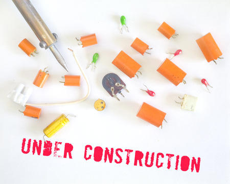 Website under construction sign with defective capacitors and soldering iron, error message Stock Photo