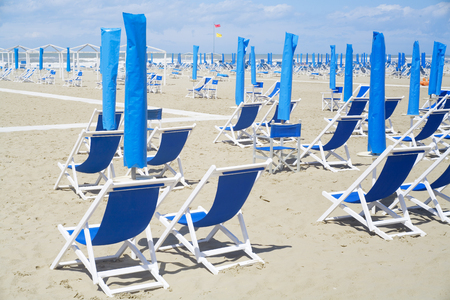 Deckchairs and sunshade on the beach at the Mediterranean seaside. Summer, holidays, vacation, travel concept.