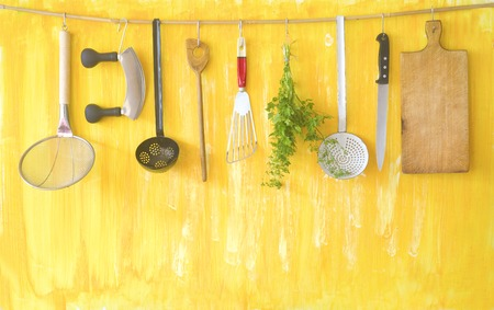 Various vintage kitchen utensils and parsley herb on a rustic wall, good copy space