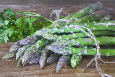 Fresh green asparagus and parsley, close up, selective focus