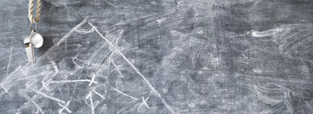 Whistle of a soccer ball referee on black board, free copy space