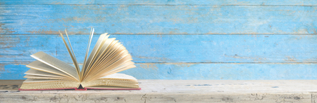 Open book on grungy blue wooden wall, panorama format good copy space. Stock Photo