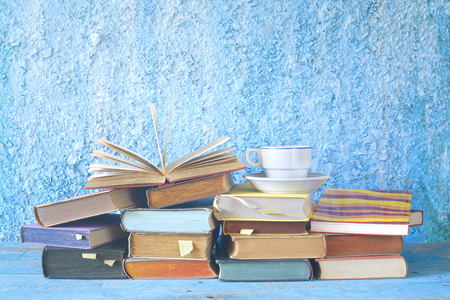 Open book on a stack of books and a cup of coffee, reading, learning, education concept, free copy space on the background. Stock Photo