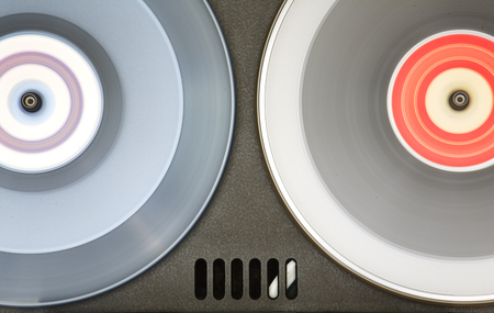Vintage open reel, reel to reel audio tape recorder, close up of two tape spools in motion. Vintage audio technology