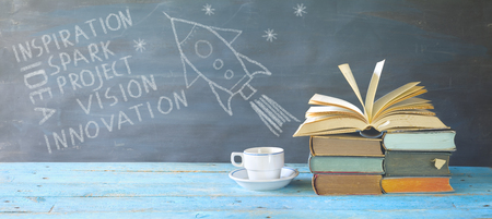 Idea, inspiration, vision concept w. books, cup of coffee, scribble on balckboard Stock Photo