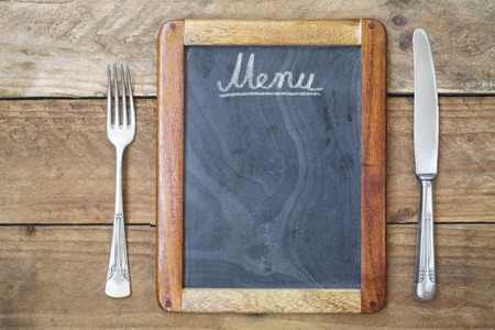 Blackboard menu with fork and knife on wooden background, free copy space Stock Photo