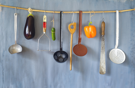 Various vintage kitchen utensils and vegetables on a rustic wall, good copy space