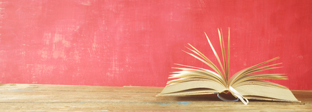 opened book on red grungy background, panoramic, good copy space, reading learning, literature concept. Stock fotó - 104872060