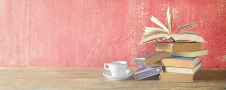 Opened Book on a pile of old books and a cup of coffee, panorama, good copy space Stock Photo