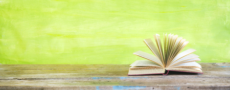 opened book on green grungy background, panoramic, good copy space Stock Photo