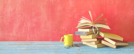 Opened Book on a pile of old books and a cup of coffee and specs, panorama, good copy space Stock Photo
