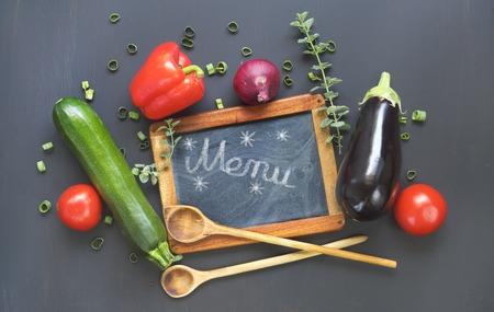 Menu template design flat lay. Black board, vegetables, good copy space