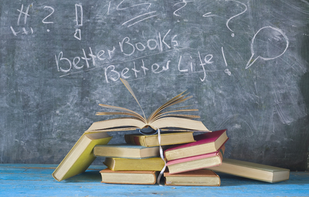 A pile of books and an open book in front of a black board