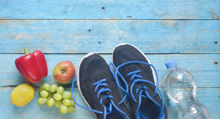 Getting fit and reducing weight for the springtime, pair of runners and fruit,free copy space,flat lay