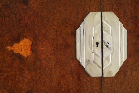 detail of a nineteen-thirties cabinet, chrome lock and high class birds eye maple veneer