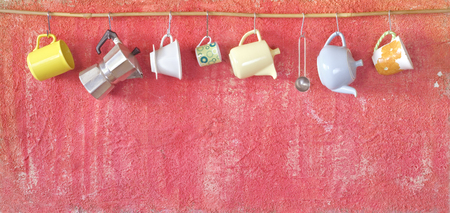 coffee pots and coffee cups hanging on a rustic wall, panorama format, good copy space