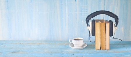 audio book concept, with book, headphones and cup of coffee, panorama, good copy space