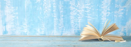 open book on blue paint background, panorama, reading education, literature, good copy space