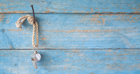whistle of a soccer  football referee, hanging on wooden planks background, free copy space