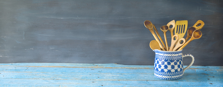old wooden spoons, kitchen utensils in an old jug, good copy space, panorama format Stock Photo