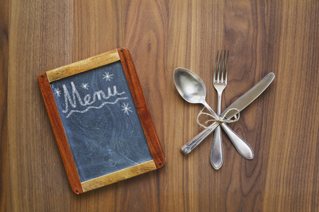 Menu blackboard with free copy space and cutlery on wooden table, flat lay Stock Photo