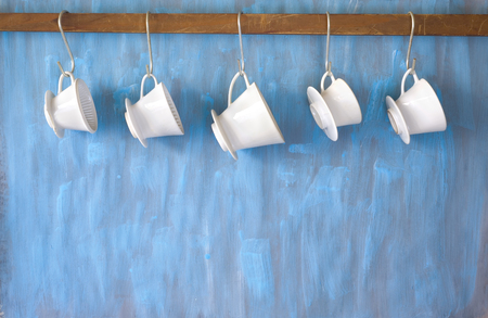 vintage porcelain coffee filters, hanging on blue background free copy space