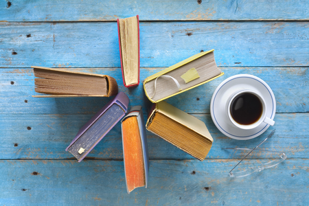 Arrangement of old books,cup of coffee and specs, free copy space.Reading, learning, lterature concept. Flat lay.