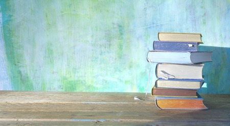 stack of books on green grungy background, panoramic, good copy space  Stock Photo