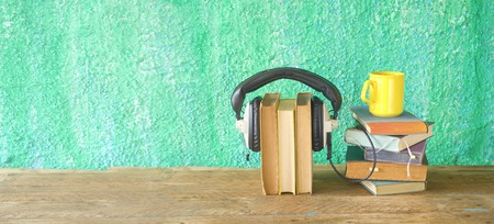audio book concept, with stacks of books, headphones and cup of coffee, panorama, good copy space  Stock Photo