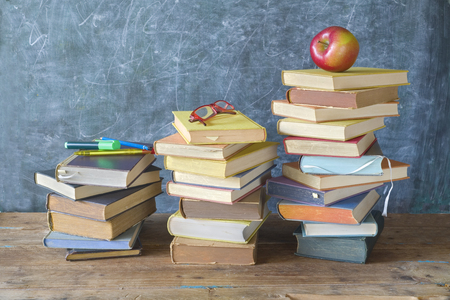 Stacks of books, apple, specs and supplies in front of a black board, back to school, good copy space
