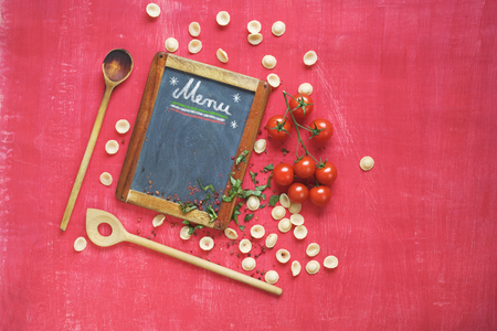 menu template for italian restaurant, orecchiette pasta, wooden spoons, tomatoes, flat lay, blackboard with free copy space