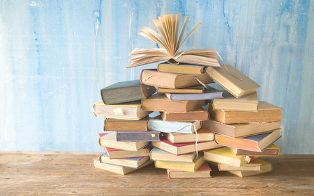 Opened book on a  large pile of books, reading education,literature, good copy space Stock Photo