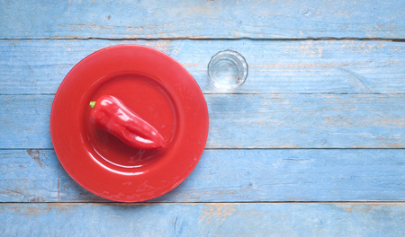 Red bell pepper on a red plate and glass of water, dieting, healthy nutrition, fitness concept, flat lay