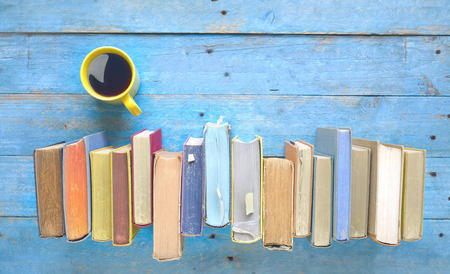 Row of old books, cup of coffee. Reading, learning, literature concept. Flat lay, large copy space. Stock Photo