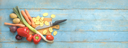 Slicing vegetables, preparing food, flat lay on rustic table, large copy space,panorama