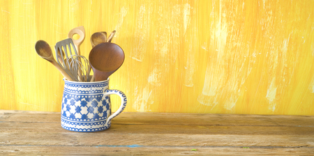 kitchen utensils in an old jug, good copy space on painted yellow wall, panorama ,large copy space