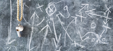 whistle of a soccer or football referee on black board with tactical diagram, free copy space 写真素材
