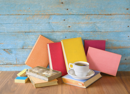 Row of multicolored hardback books and cup of coffee, reading education, literature, good copy space