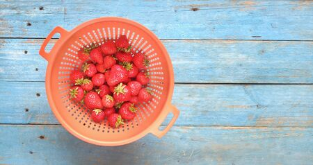 red wild strawberries on old blue wooden table, flat lay good copy space