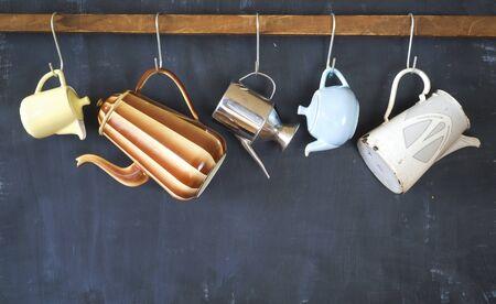 vintage coffee pots hanging with dark background, free copy space Banco de Imagens
