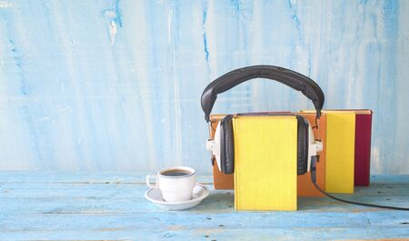 audio book concept with book, headphones and cup of coffee, panorama format on grungy background, good copy space Banco de Imagens