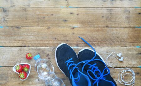 fitness, sport and reducing weight in the summer, pair of runners water,strawberris,headphones,free copy space, flat lay