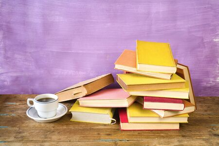 Pile of old books and a cup of coffee. Reading, learning, education, literature concept, panorama, good copy space