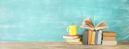 Libro aperto e pila di libri con copertina rigida multicolori con una tazza di caffè, lettura educazione, letteratura, panoramica, buona copia spazio Archivio Fotografico