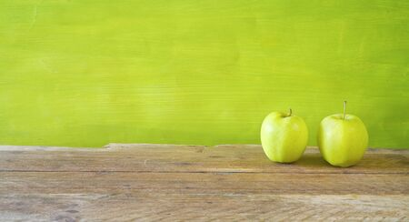 dieting and healthy food concept with two green apples on green background, panoramic mock up with free copy space Reklamní fotografie