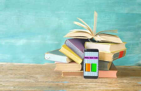 Stack of books and smartphone. online book shop, E- Book, book fair, reading,education concept.