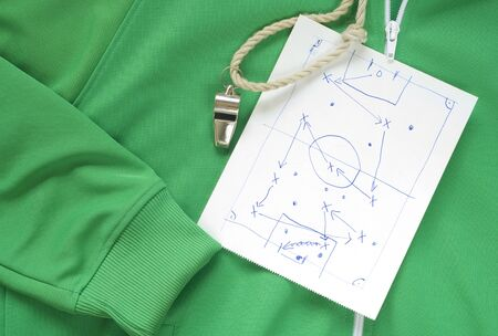 whistle of a soccer or football referee or coach and a tactical diagram scribble on a track suit