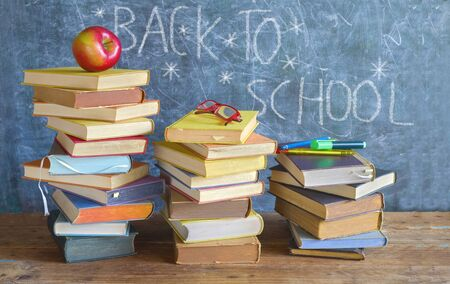 Back to school, stacks of books, apple, specs and school supplies in front of a black board Reklamní fotografie